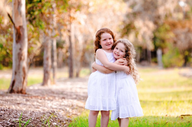 Two sisters hugging at their kids photography session.