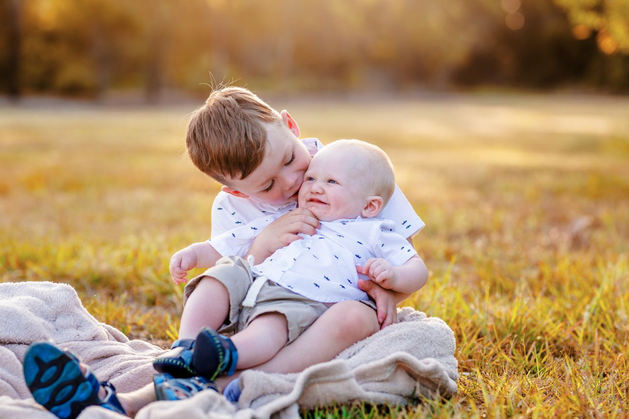 A portrait of two young brothers kissing each other in the grass.