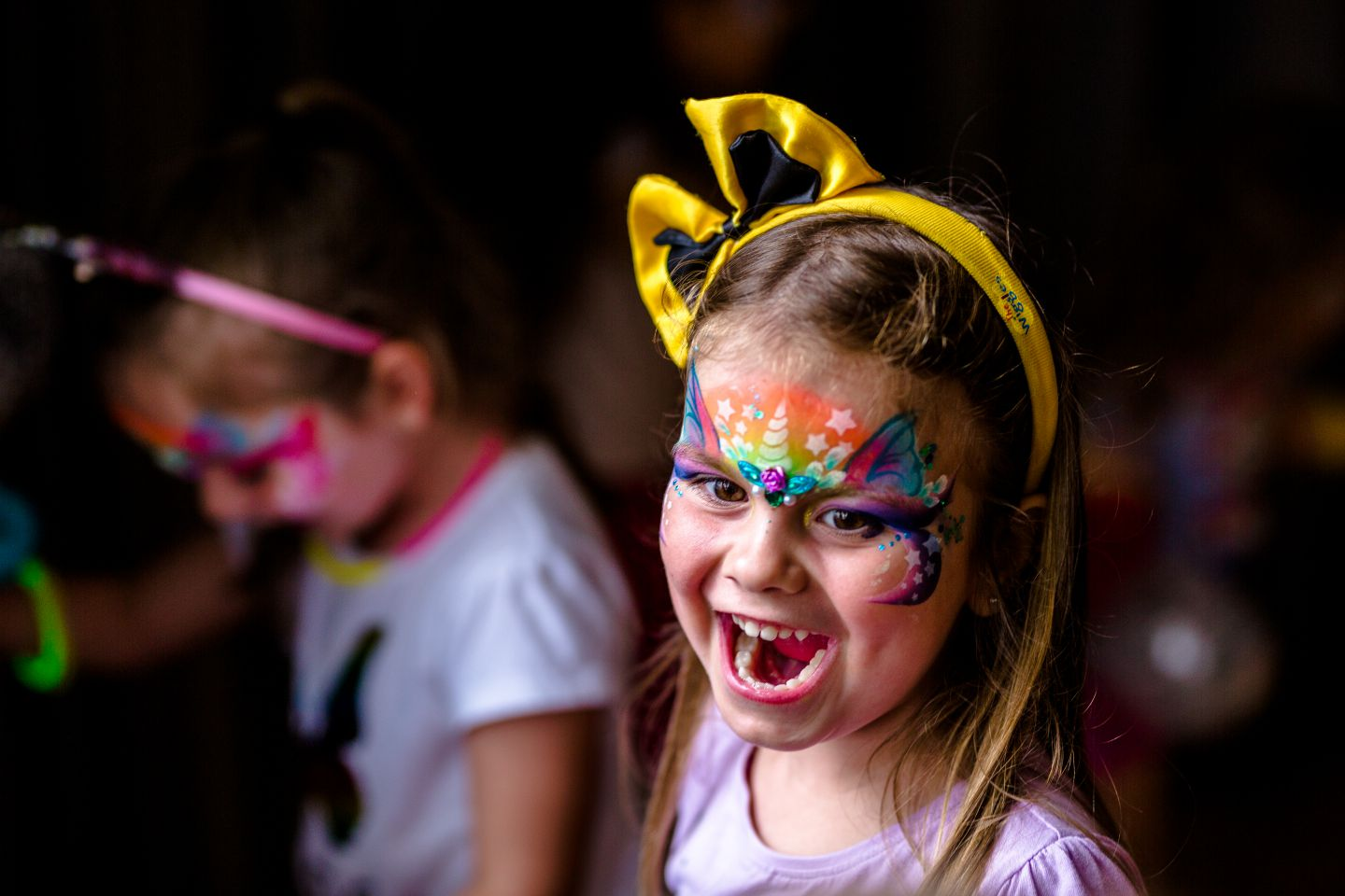 A girl wearing a unicorn face mask laughing at a children's party.