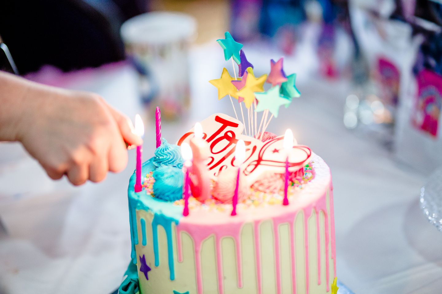 A JoJo Siwa birthday cake that is getting lit at a children's birthday party.