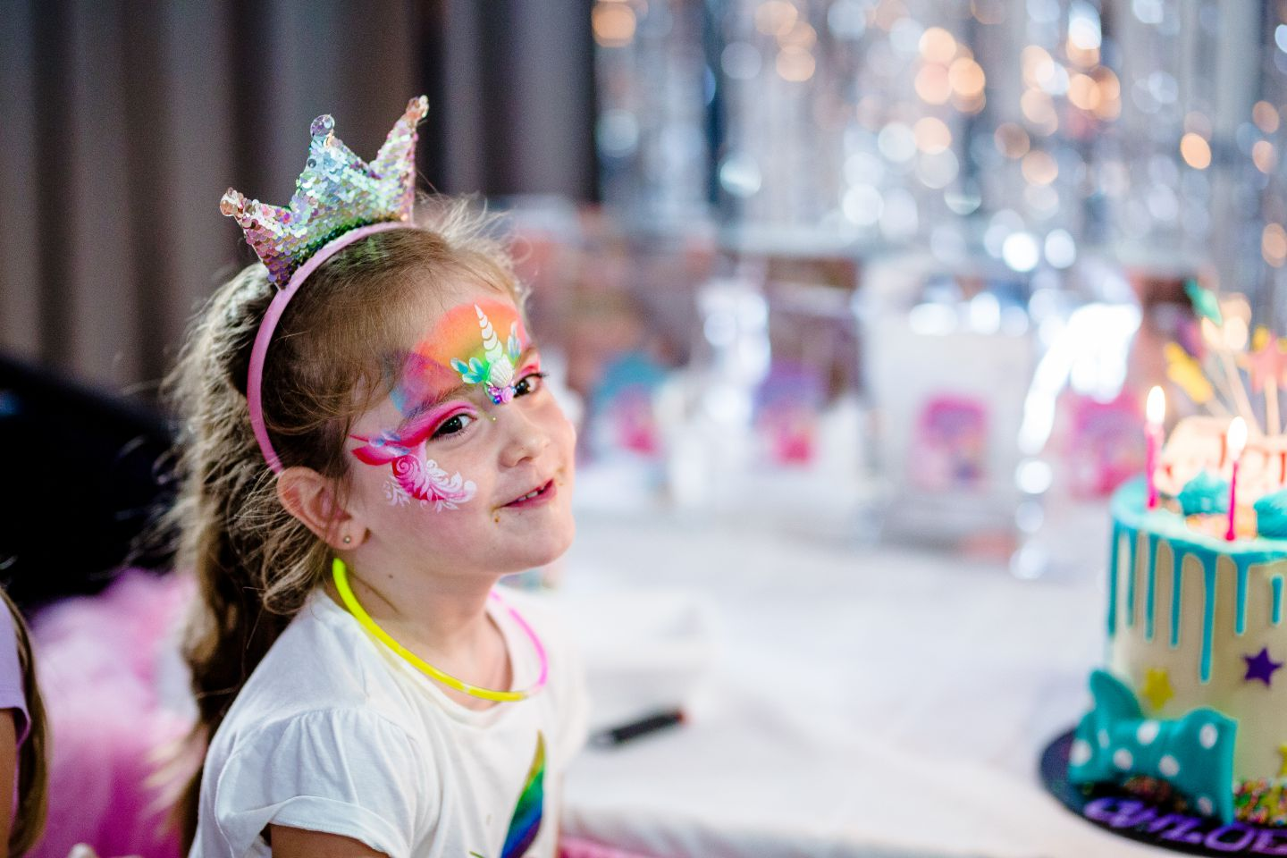 A young girl at Caboolture smiling. She has unicorn face paint on.