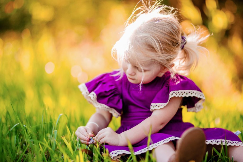 A young girl in purple plays with a glittery gem in the grass.