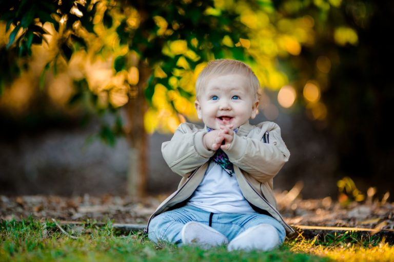 A young boy in Narangba is clapping and smiling while staring at the camera.