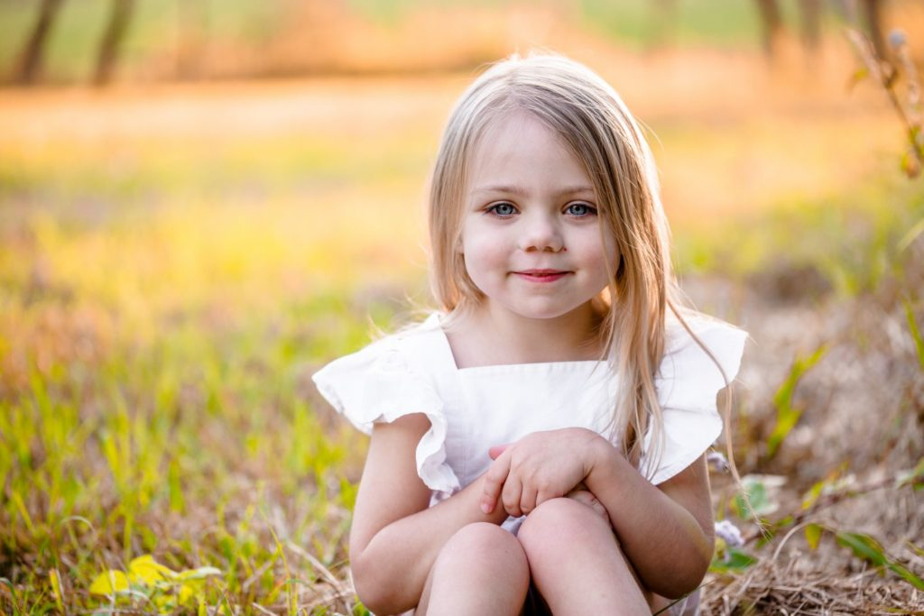 A girl wearing a white dress sits in front of the camera at Burpengary with a slight smile.