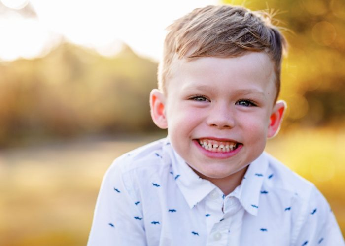 A boy smiles at the camera at his family portrait photography session.