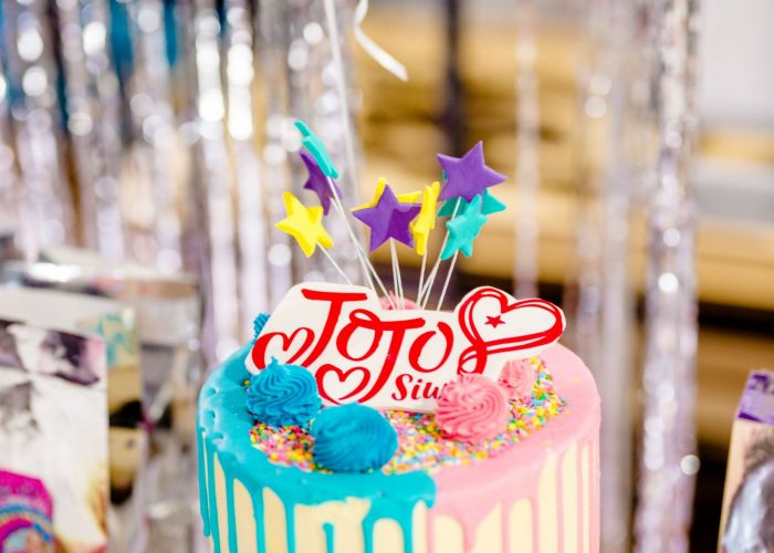 A Jojo Siwa birthday cake on a table full of food at a birthday party in Caboolture.